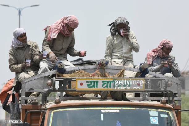 Group of labourers sitting atop a truck drink flavoured water, distributed by local residents as a goodwill gesture on a summer day, at Chattarpur,...