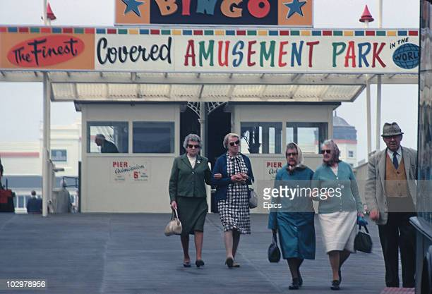 A group of ladies and a man walk in front of the amusement park at the seaside town of WestonsuperMare Somerset May 1970