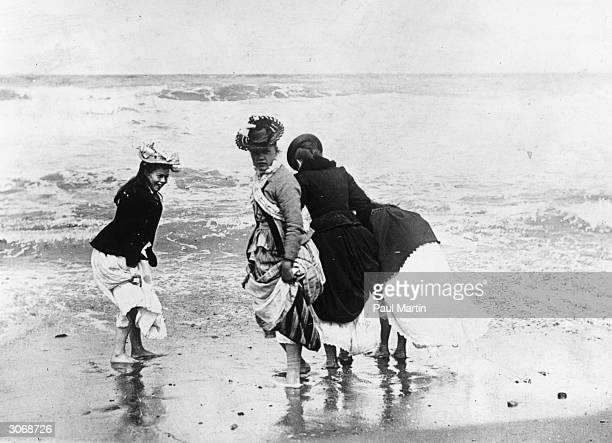 A group of ladies brave the waves on a British beach