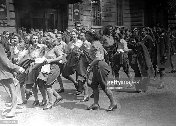 A group of Land Girls dance among crowds heading towards Trafalgar Square as they celebrate Victory in Europe Day to mark the end of European...