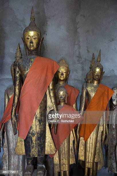 group of laotian buddhas with saffron cloth - laotian culture stock pictures, royalty-free photos & images