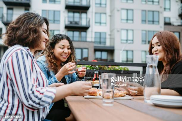 group of latina friends eat on outdoor patio - tacoma stock pictures, royalty-free photos & images