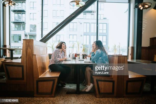 group of latina friends out for brunch - diner stock pictures, royalty-free photos & images