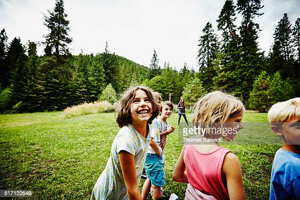 Group of laughing kids standing in grass field