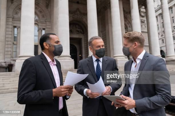 group of lawyers wearing facemasks outside a court - lawyer stock pictures, royalty-free photos & images