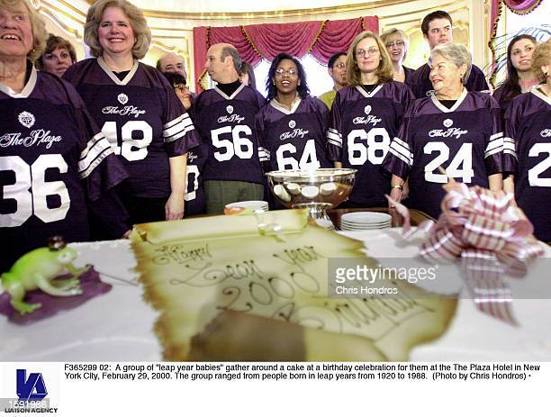 A group of leap year babies gather around a cake at a birthday celebration for them at the The Plaza Hotel in New York City February 29 2000 The...
