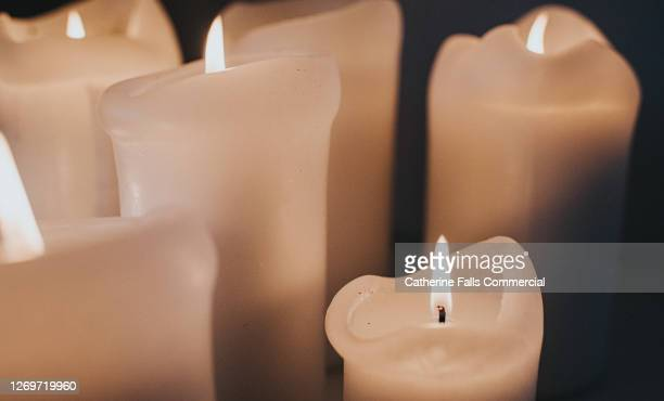 group of lit white candles flickering in the darkness - religious vigil stock pictures, royalty-free photos & images