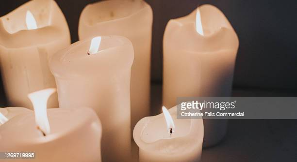 group of lit white candles flickering in the darkness - memorial vigil stock pictures, royalty-free photos & images