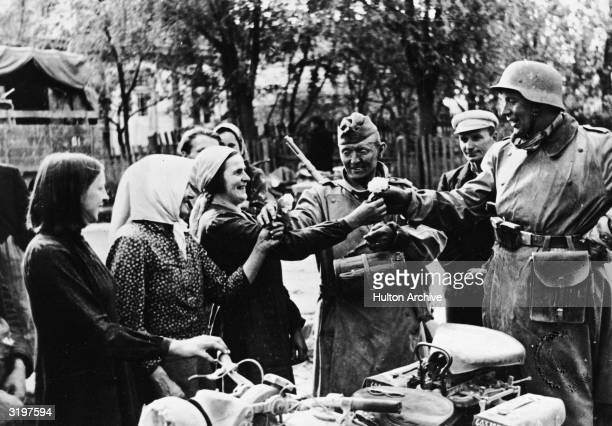 A group of Lithuanian women greet the arrival of German troops with flowers late June 1941