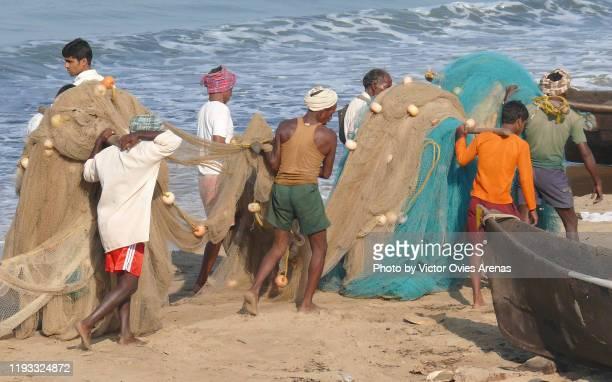 group of local fishermen carrying their fishing nets on the beach in gokarna, karnataka, india - victor ovies fotografías e imágenes de stock
