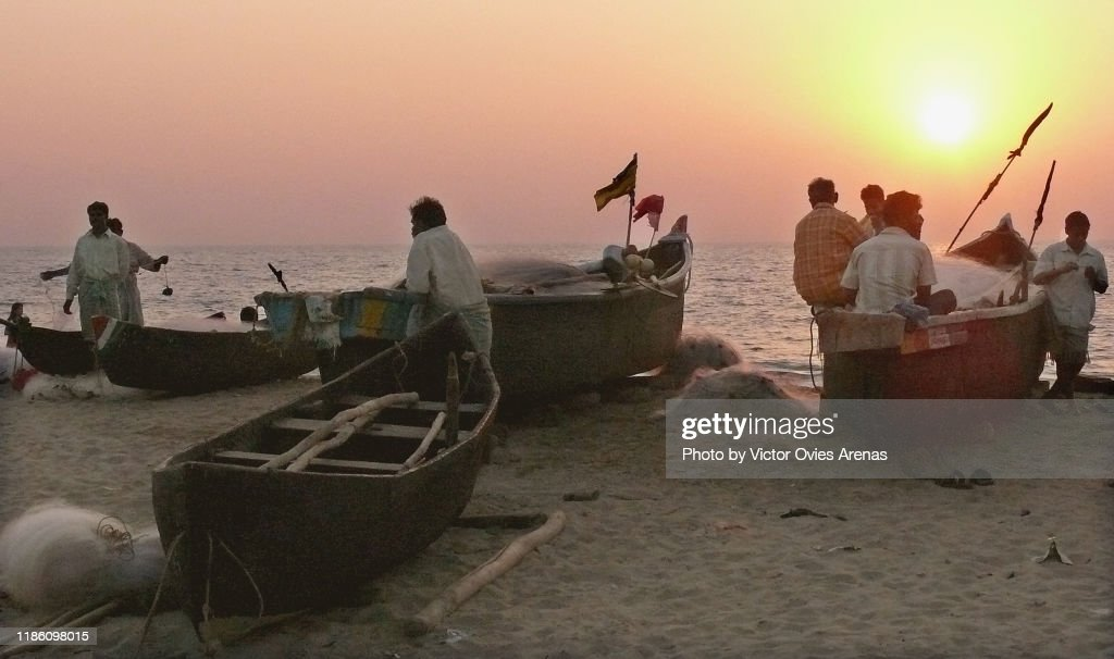 Group of local fishermen sitting on their boats at sunset on the beach in Gokarna, Karnataka, India : Foto de stock