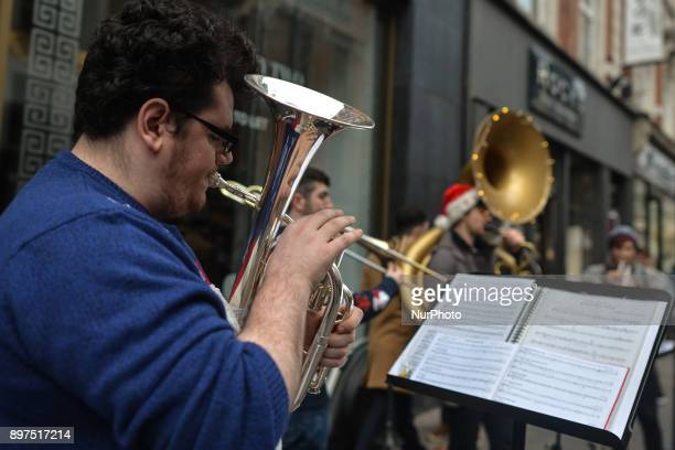 A group of local musicians using wind instruments busk on Grafton Street in Dublin's city center On Friday 22 December 2017 in Dublin Ireland