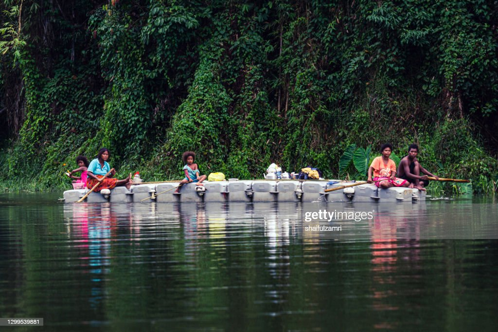 Group of local people paddling a boat going home as part of daily life on Royal Belum Rainforest Park. : Stock Photo