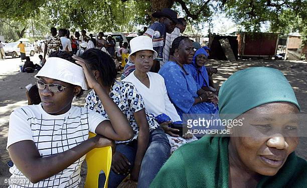 A group of local residents in Gaborone Botswana spend hours in the hot sun 30 October 2004 waiting to cast their vote in the countries election Some...