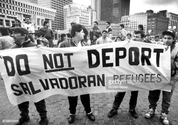 A group of local Salvadorans hold a sign during a vigil on Boston City Hall Plaza calling for the extension of the temporary protected status of...