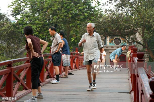 Group of local seniors exercising at a wooden bridge at the Hoan Kiem Lake in Hanoi, Vietnam in the morning.