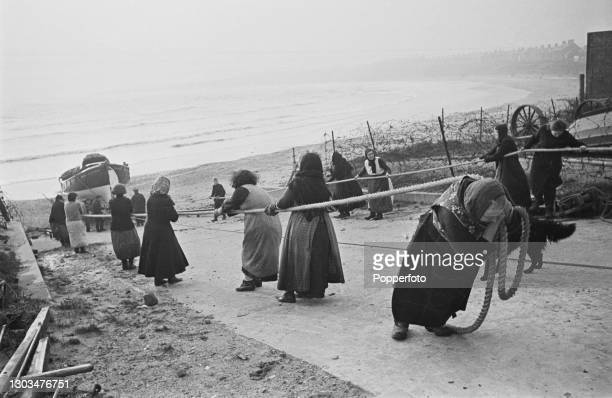 Group of local women use ropes to haul the Royal National Lifeboat Institution Newbiggin lifeboat up the slipway to the lifeboat station on the shore...