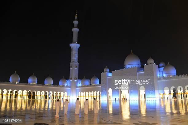 groep van de lokale bevolking in sheikh zayed moskee bij nacht, abu dhabi, verenigde arabische emiraten - vijf personen stockfoto's en -beelden