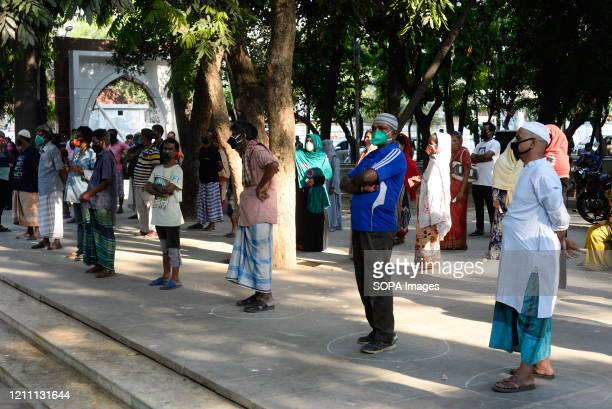 Group of low-income earners stand in a queue to receive relief supplies. During the Coronavirus crisis besides the government, many organisations are...