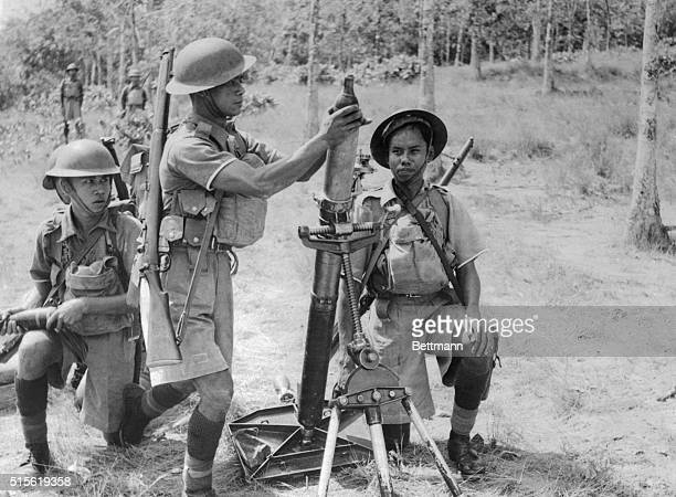 A group of Malaysian soldiers under the command of the British prepare to fire a mortar during a battle on the Malay Peninsula