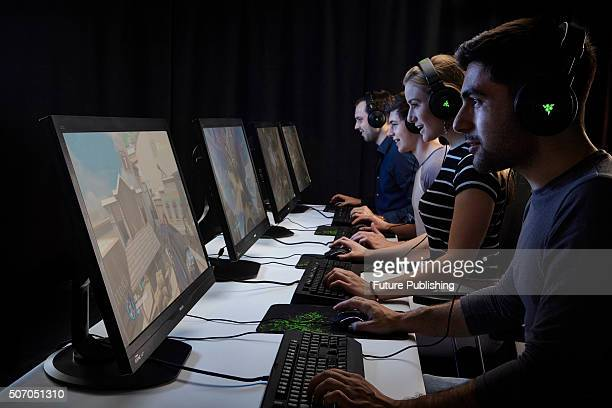 A group of male and female gamers playing PC games while wearing headsets taken on November 6 2015