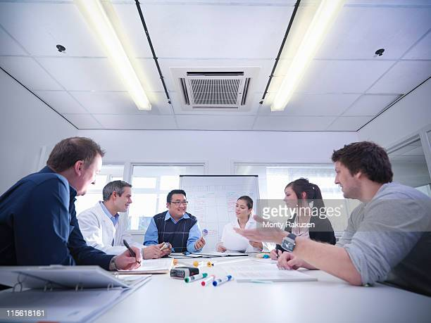 Group of male and female scientists sat round table discussing product prototypes