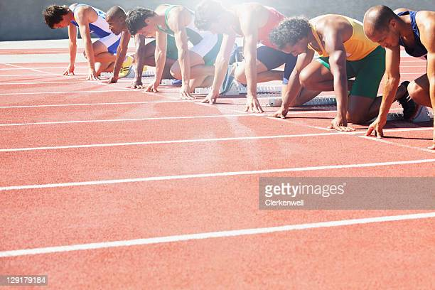 group of male athletes at start of running track - athleticism stock pictures, royalty-free photos & images