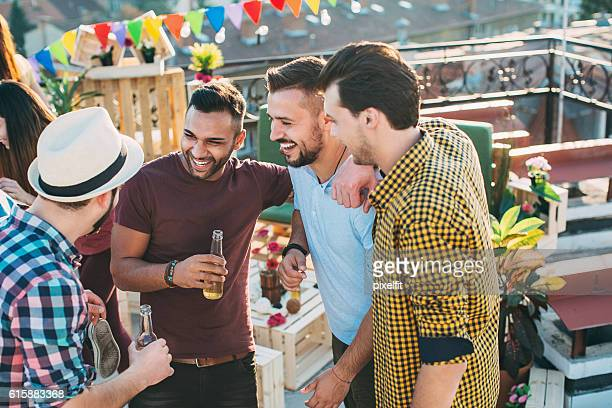 Group of male friends chatting and drinking