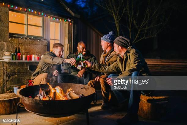 Gruppe von männlichen Freunde versammelten sich um eine Feuerstelle