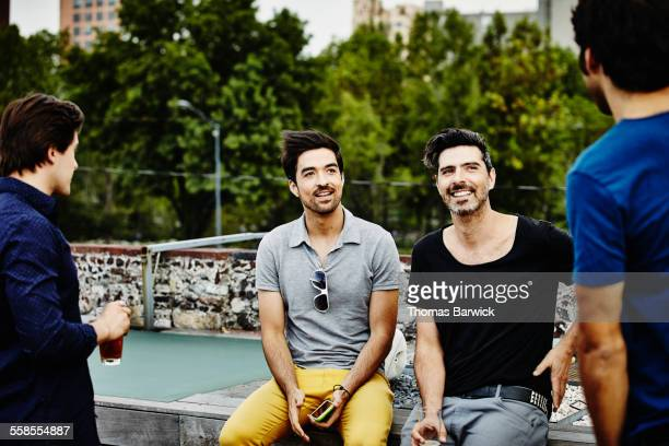 group of male friends sharing drinks on rooftop - handsome mexican men stock pictures, royalty-free photos & images