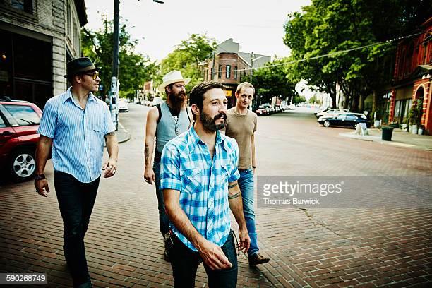 Group of male friends walking on city street