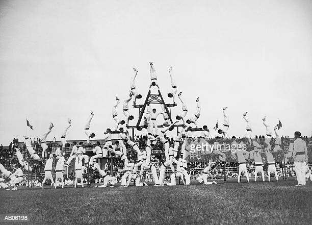 group of male gymnasts forming pyramid on athletic field (b&w) - human pyramid stock photos and pictures