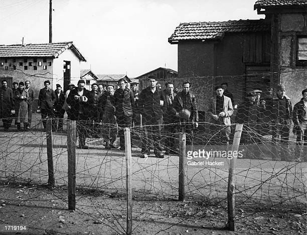 A group of male prisoners stand behind a wire fence in section B of Le Vernet Concentration Camp France circa 1943 The men were political enemies of...