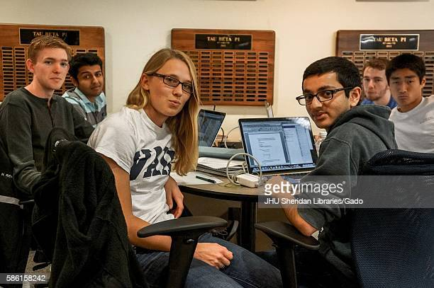 Group of male students and one female student seated at a table with laptops and notebooks turns around to pose for a photograph in the library,...