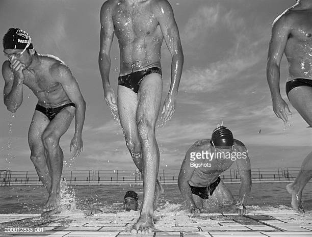 group of male swimmers getting out of swimming pool (b&w) - young men in speedos stock photos and pictures