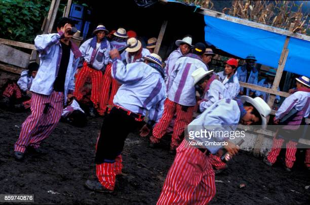 A group of Mam Mayan men drinking dancing and laying down in the mud during the festival of All Saints' Day and the Day of the Dead on November 1st...