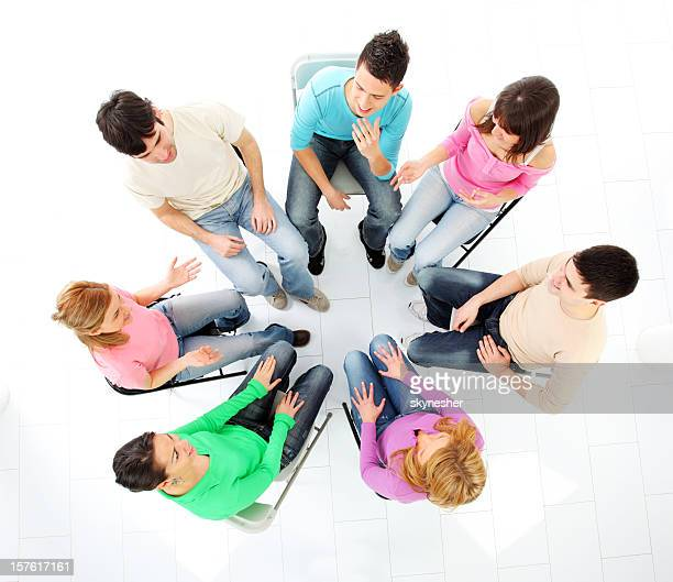 Group of many young people sitting in circle and discussing.