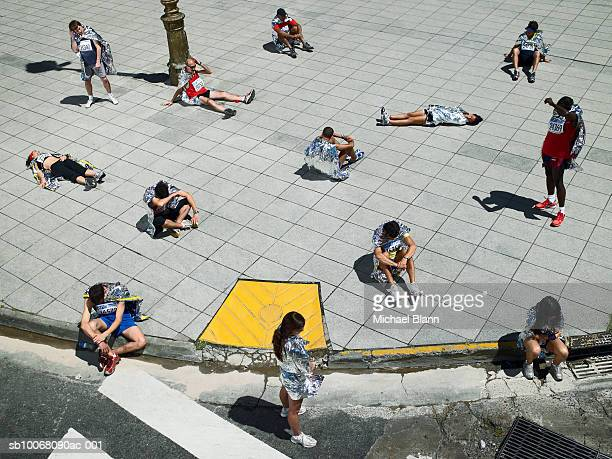 Group of marathon runners relaxing on pavement, all wrapped in blankets
