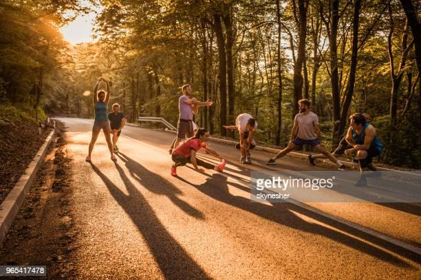 gruppe von marathonläufer aufwärmen auf einer straße bei sonnenuntergang. - körperbewusstsein stock-fotos und bilder