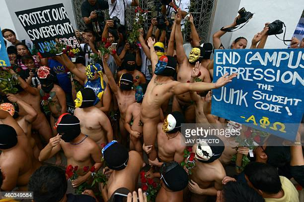 A group of masked fraternity members in the staterun University of the Philippines hoist up a comrade as they prepare to run naked through the campus...