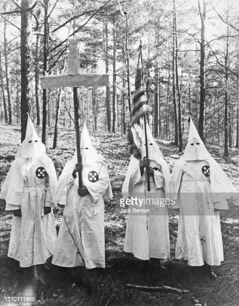 Group of masked Ku Klux Klan members upholding a cross and an american flag, US, circa 1920.