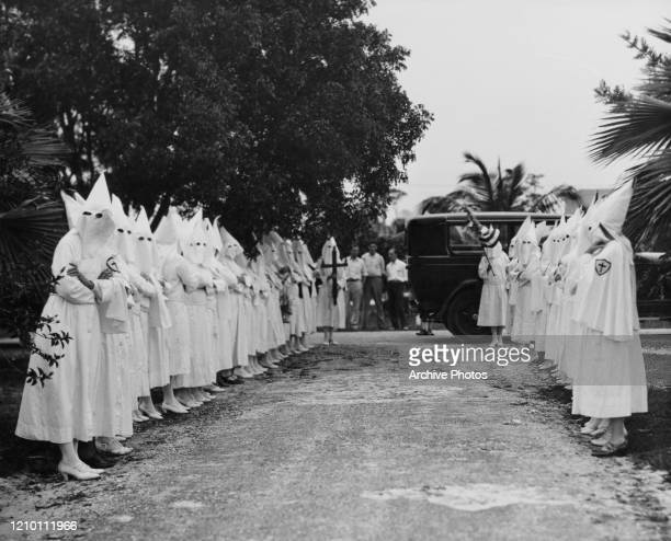 Group of masked Ku Klux Klan women lined up on both sides of a road upholding a cross and a flag, US, circa 1940.
