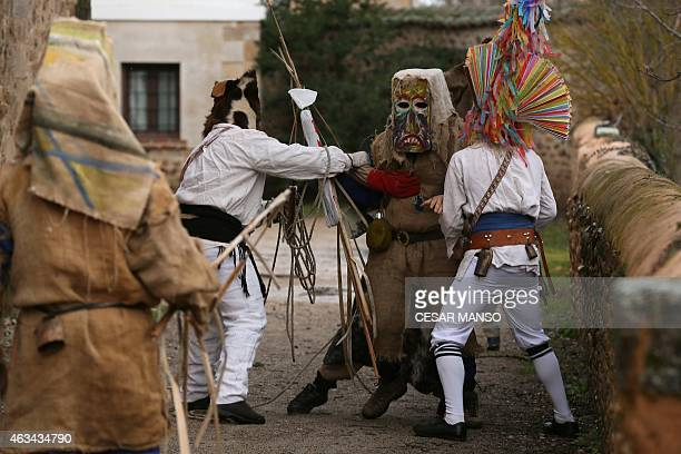 A group of masked men dressed as Antruejos carrying cowbells tied to his back take part in the carnival of Carrizo de la Ribera in the northern...