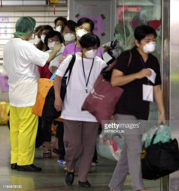 A group of masked nurses and patients walk out of the Taipei Municipal Hoping Hospital 04 May 2003 carrying their personal belongings towards a...