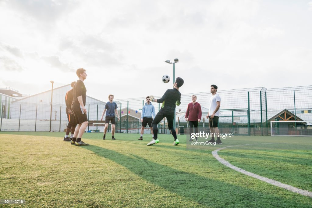A group of mates playing keepy-uppy : Stock Photo