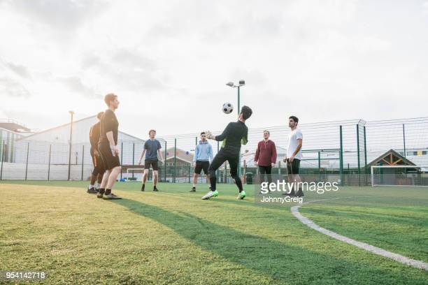 a group of mates playing keepy-uppy - soccer stock pictures, royalty-free photos & images
