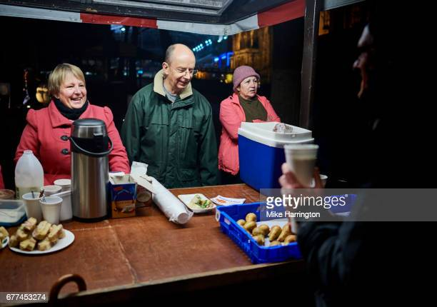 group of mature adults volunteering at their local soup kitchen - charity and relief work stock pictures, royalty-free photos & images