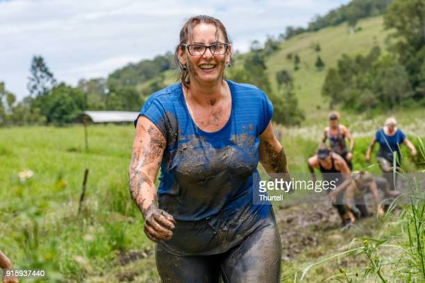 Group Of Mature Age Women Participating In Mud Run Fitness Training Together