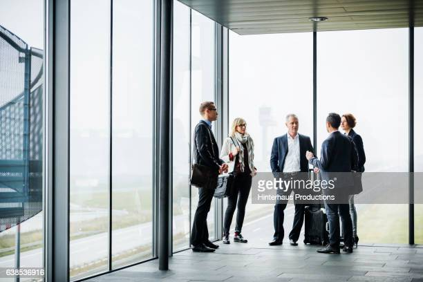 group of mature business travellers meeting at the airport and talking - geschäftsleute stock-fotos und bilder