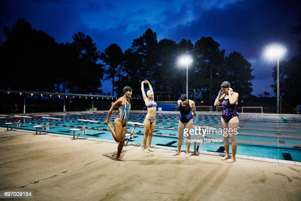 Group of mature female swimmers stretching before early morning workout at outdoor pool